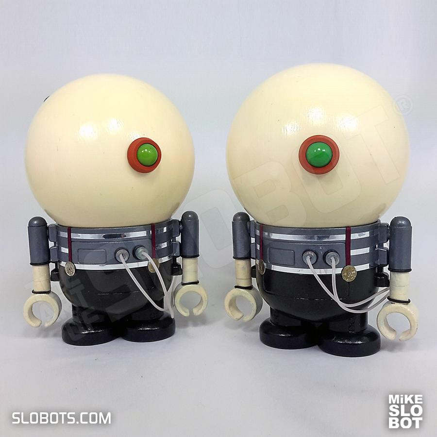 This is a diptych work of art depicting Tweedledee and Tweedledum of Alice in Wonderland as robots. This is the view from the front.